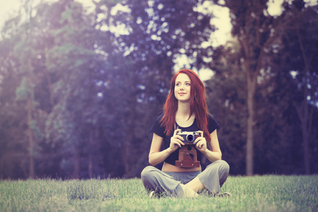 indie: Young girl in indie style clothes with retro camera on green grass in the park