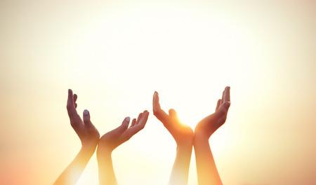 dva: čtyři ruce na pozadí při západu slunce.
