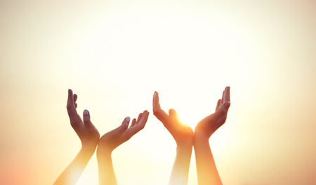 mano de dios: cuatro manos en el fondo la puesta del sol.