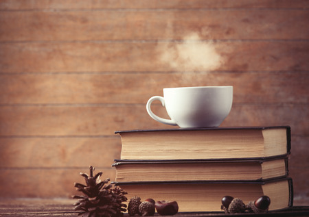 cafe: Cup of coffee and pine cone with books on wooden background
