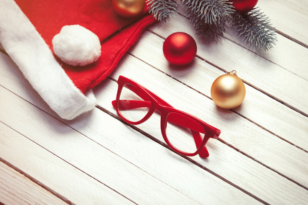 christmas bubbles: Santas hat and christmas bubbles with red glasses on white wooden table.
