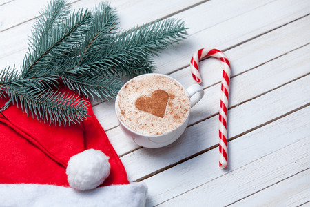 Cup of coffee with heart shape and christmas candy near brench on white wooden background. Archivio Fotografico