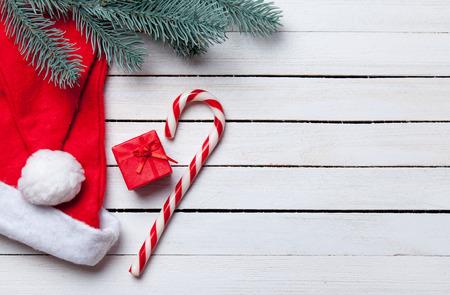 サンタ帽子とクリスマス キャンディ ホワイト木製テーブルの上の brench と赤のギフト。 写真素材