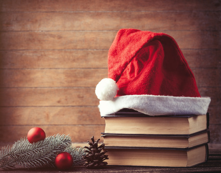 christmas hats: Santas hat and pine brench with books on wooden table.