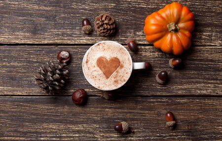 Cup of coffee with heart shape and pine cone with acorn and pumpkin on wooden background Imagens