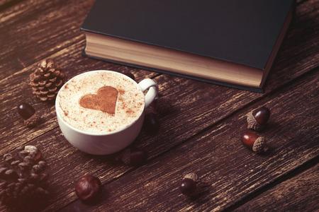 desayuno romantico: Taza de caf� con forma de coraz�n y el cono del pino con la bellota, libro sobre fondo de madera