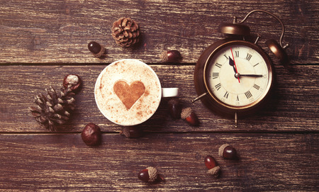 acorn: Cup of coffee with heart shape and pine cone with acorn and clock on wooden background