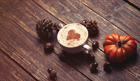 acorn: Cup of coffee with heart shape and pine cone with acorn and pumpkin on wooden background Stock Photo