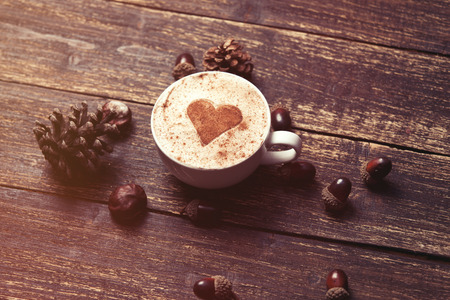 to fall in love: Cup of coffee with heart shape and pine cone with acorn on wooden background