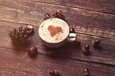 desayuno romantico: Taza de café con forma de corazón y el cono del pino con la bellota en el fondo de madera Foto de archivo