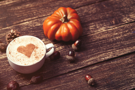 Cup of coffee with heart shape and pine cone with acorn and pumpkin on wooden background 写真素材