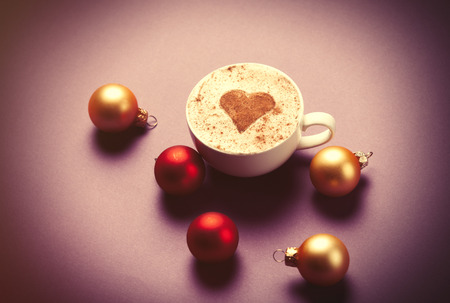 christmas bubbles: Cup of coffee with heart shape and christmas bubbles around. Photo in old color image style.
