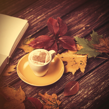 autumn colour: Autumn leafs, book and coffee cup on wooden table.