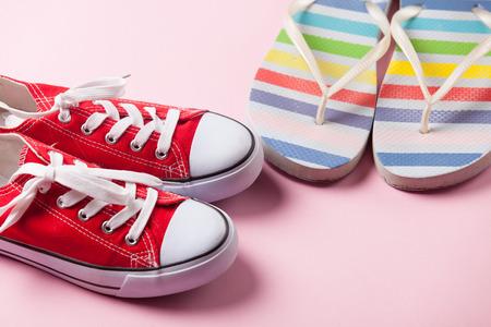 flip flops: Gumshoes and flip flops on pink background. Stock Photo