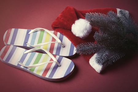 flip flops: Flip flops and Santas hat on red background. Stock Photo