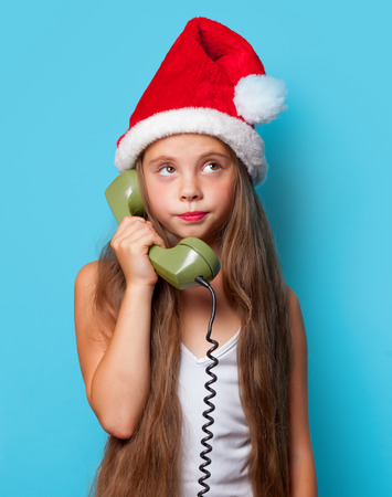 landline phone: Young surprisd girl in Santas hat calling by phone on blue background. Stock Photo