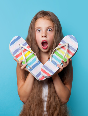 flops: Young surprised girl with flip flops on blue background.