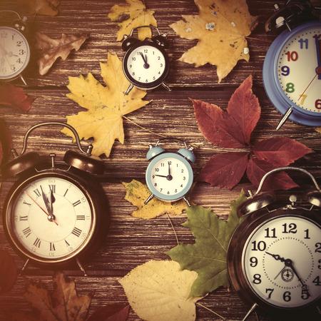 Hojas de otoño y reloj despertador en la mesa de madera. Foto de archivo
