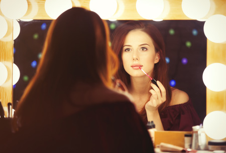 mirror: Portrait of a beautiful woman as applying makeup near a mirror. Photo in retro color style.