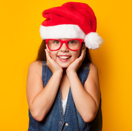 girl glasses: Beautiful young girl in red glasses and Santas hat on yellow background. Stock Photo
