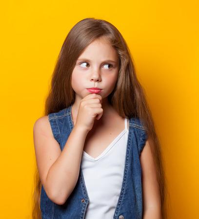 petite fille triste: Jeune fille triste sur fond jaune.
