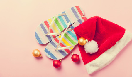 flip flops: Santas hat and flip flops on pink background. Stock Photo