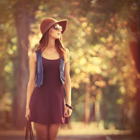 beautiful redhead: Beautiful redhead girl with bag in the park.
