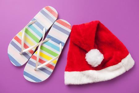 flip flops: Santas hat and flip flops on violet background.