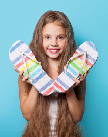 flip flops: Young smiling girl with flip flops on blue background.