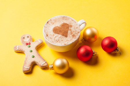 christmas bubbles: Cup of coffee and gingerbread with christmas bubbles on yellow background.