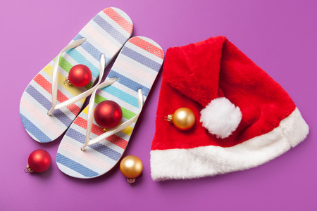 christmas bubbles: Santas hat and flip flops with christmas bubbles on violet background. Stock Photo