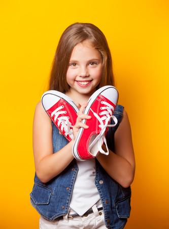 노란색 배경에 빨간색 gumshoes와 젊은 웃는 소녀. 스톡 콘텐츠