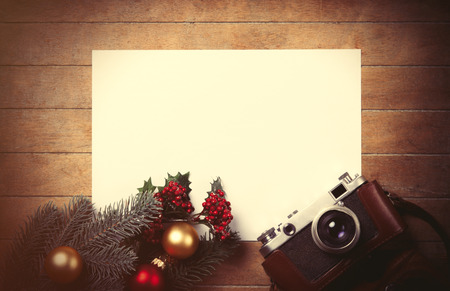 camera: White papaer and christmas toys with fir-tree branch and camera on wooden background.