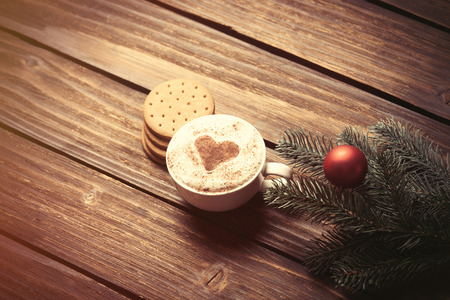 christmas bubbles: Cup of coffee and branch with christmas bubbles on wooden table. Stock Photo