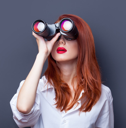 Portrait of a surprised businesswomen in white shirt with binocular on grey background.