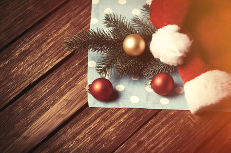 christmas bubbles: Santas hat and christmas bubbles on wooden table. Stock Photo