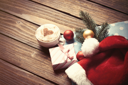 christmas bubbles: Cup of coffee and gift box with christmas bubbles on wooden table.