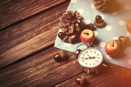 reloj: Despertador y pi�as en mesa de madera.