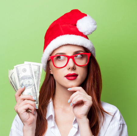business christmas: Portrait of a women in christmas hat with money on green background. Stock Photo
