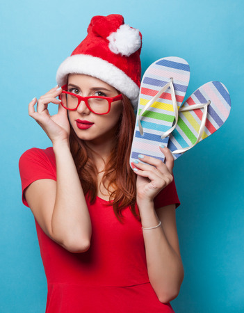 flip flops: women in christmas hat with flip flops on blue background.