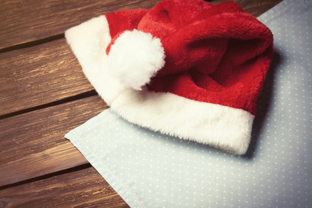 servilleta de papel: Red Santas hat and serviette on wooden table Foto de archivo
