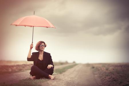 lluvia paraguas: Mujeres jóvenes estilo con el paraguas en el campo al aire libre. Fotos en estilo antiguo color de la imagen. Foto de archivo