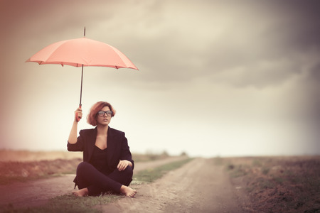 umbrella rain: Style young women with umbrella at countryside outdoor. Photo in old color image style. Stock Photo