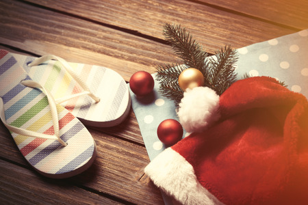 christmas bubbles: Santas hat and christmas bubbles with flip flops on wooden table.