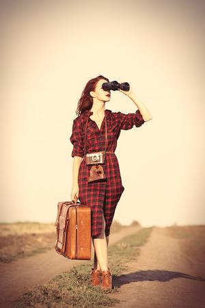 格子縞のドレス バッグと田舎で双眼鏡で美しい少女