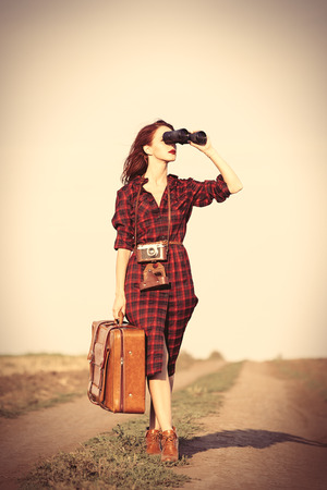 Beautiful girl in plaid dress with bag and binocular on countryside Foto de archivo