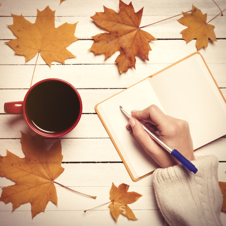 writing black: Female hand writing something in notebook near cup of coffee. Stock Photo
