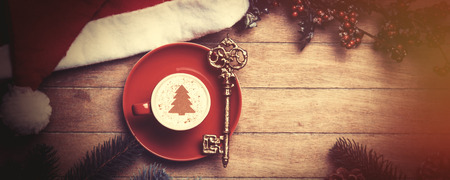 warm color: Cappuccino with key on wooden table.