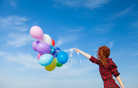 blue plaid: Beautiful girl in plaid dress with multicolored balloons on blue sky background