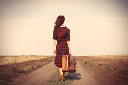 Mooie meisje in geruite jurk met zak op het platteland